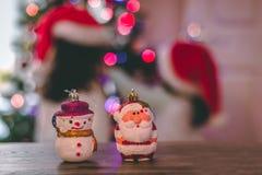 Chucherías del muñeco de nieve y de Papá Noel con las luces y los niños de la Navidad en el fondo Fotografía de archivo