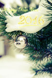 Chucherías que cuelgan en un árbol de navidad cubierto con nieve Toni retro Imágenes de archivo libres de regalías