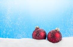 Chucherías rojas con nieve que cae Fotos de archivo
