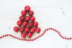 Chucherías rojas de la Navidad en la forma de un árbol de abeto en el painte blanco Foto de archivo