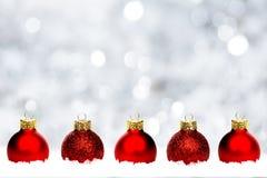 Chucherías rojas de la Navidad en nieve con el fondo de plata Fotos de archivo