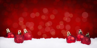 Chucherías rojas de la Navidad en nieve con un fondo rojo fotografía de archivo libre de regalías