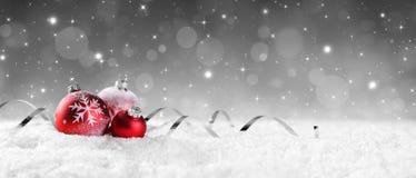 Chucherías rojas en nieve con las estrellas chispeantes Imagen de archivo