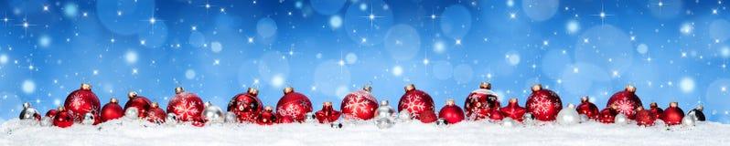 Chucherías rojas en nieve con las nevadas y el cielo azul Foto de archivo libre de regalías