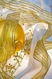 Chucherías y cintas de oro de la Navidad Fotos de archivo