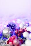 Chucherías y ornamentos de plata de la Navidad contra luces festivas Foto de archivo libre de regalías