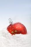 Chuchería roja de la Navidad en la nieve Imágenes de archivo libres de regalías