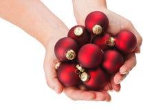 Chucherías rojas de la Navidad en manos Fotografía de archivo