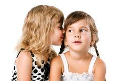 Chuchotement de deux petites filles d'isolement au-dessus du blanc Photos stock