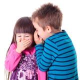 Chuchotement de petit garçon et de fille Photographie stock