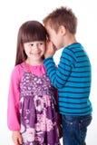 Chuchotement de petit garçon et de fille Photos stock