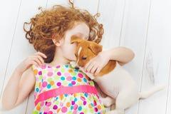 Chuchotements de petite fille et de chiot sur le fond en bois Photographie stock