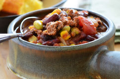 Chuckwagon chili con carne. Hearty bowl of chuckwagon chili con carne with beef, beans, corn, tomato and cornbread Royalty Free Stock Photography