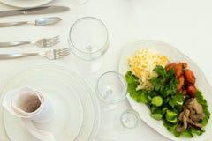 Chucrut, setas, tomates, pepinos, lechuga Plato del menú con bocados fríos Placas, servilletas, bifurcaciones, cuchillos, vidrio imagenes de archivo