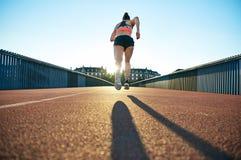 Chudego sportowego żeńskiego biegacza złapany w połowie lot Fotografia Royalty Free