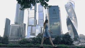 Chuderlawa dziewczyna w błękit sukni odprowadzeniu przeciw nowożytnym szklistym drapaczom chmur Bielący kolory Super zwolnione te zdjęcie wideo