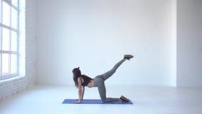 Chuderlawa sportowa kobieta w robić ćwiczenie osła kopnięciu na joga macie w białym studiu 4k materiał filmowy zbiory wideo