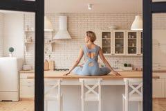 Chuderlawy blondynki kobiety obsiadanie na stole w lotosowej pozie fotografia stock