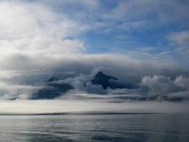 Chugach Mountains Covered With Mist. Early morning mist covers the Chugach Mountains over the Bay of Valdez, Alaska. Blue sky breaks through cloud cover stock image