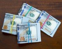 Chuje sto dolarowych rachunków na drewnianym stole Zdjęcia Stock