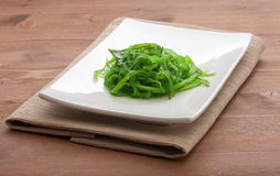 Chuka seaweed. White plate with chuka seaweed and napkin on the wooden table Stock Images