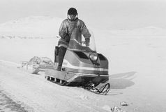 Chukchi man drives snowmobile in tundra Royalty Free Stock Photography