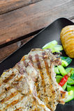 Chuleta asada a la parrilla con las verduras y las patatas asadas fotografía de archivo