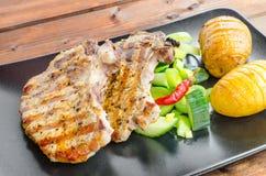 Chuleta asada a la parrilla con las verduras y las patatas asadas imagen de archivo
