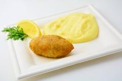 Chuleta con el puré de patata en la placa de la casilla blanca, aislada Fotos de archivo