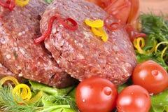 Chuleta cruda fresca de la hamburguesa con las hierbas y los tomates Fotografía de archivo
