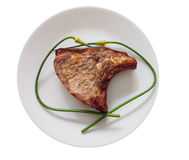 Chuleta de cerdo con los scapes del ajo en una placa foto de archivo