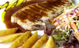 Chuleta de cerdo y salsa con las fritadas y la ensalada Foto de archivo