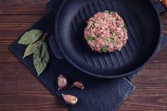 Chuleta de la carne cruda con las hierbas en una cacerola del arrabio en una piedra con el ajo, fondo de madera marrón Foto de archivo libre de regalías