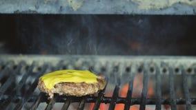 Chuleta del cheeseburger cocinada para un partido de la barbacoa en un fin de semana festivo en la parrilla del josper almacen de metraje de vídeo