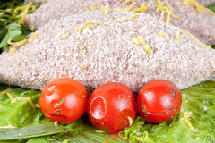 Chuleta empanada cruda de los pescados con los tomates de cereza de la ensalada Foto de archivo libre de regalías