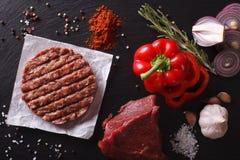 Chuletas crudas del filete de la hamburguesa de la carne picada con los ingredientes horizonta Foto de archivo libre de regalías