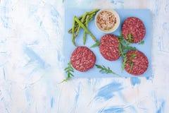 Chuletas crudas para la barbacoa Carne para cocinar el almuerzo y especias y espárrago Barra de la aptitud de los cereales para l imagenes de archivo