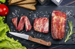 Chuletas de cerdo asadas a la parrilla del cerdo en un tablero Imagen de archivo