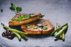 Chuletas de cerdo asadas a la parrilla, filetes con las verduras, habas y salsa en una pizarra negra Carne fresca con espuma Fond Foto de archivo libre de regalías