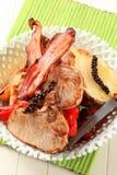 Chuletas de cerdo con la patata y las pimientas rojas Foto de archivo libre de regalías