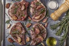 Chuletas de cerdo crudas con las especias en un molde para el horno del metal Imagenes de archivo