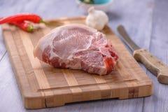 Chuletas de cerdo crudas en la tabla de cortar Foto de archivo libre de regalías