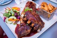 Chuletas de cerdo del Bbq con las fritadas y la ensalada Imagen de archivo