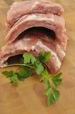 Chuletas de cerdo del cerdo en la tajadera de madera Fotografía de archivo