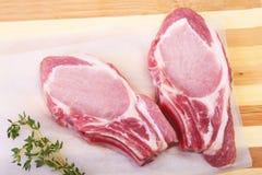 Chuletas de cerdo, especias y romero crudos en tabla de cortar Aliste para cocinar Fotografía de archivo
