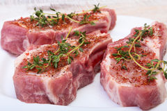 Chuletas de cerdo, especias y romero crudos en tabla de cortar Aliste para cocinar Fotografía de archivo libre de regalías