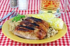 Chuletas de cerdo, maíz y arroz asados a la parilla Foto de archivo libre de regalías