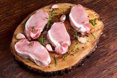 Chuletas de cerdo sin hueso frescas crudas con las hierbas En el tablero de madera Fotos de archivo