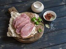 Chuletas de cerdo y especias crudas en una tabla de cortar de madera rústica Imágenes de archivo libres de regalías