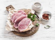 Chuletas de cerdo y especias crudas en una tabla de cortar de madera rústica Foto de archivo libre de regalías